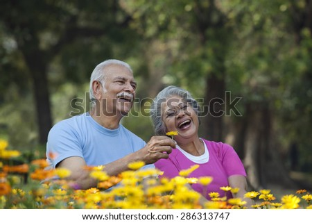 Happy senior man smiling with woman at park holding flower