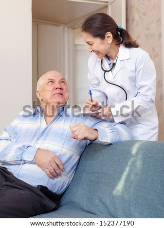 Happy senior man tells the mature doctor the symptoms of malaise - stock photo