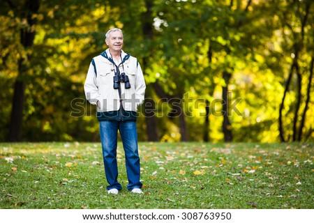 Happy senior man walking in the park with binoculars - stock photo