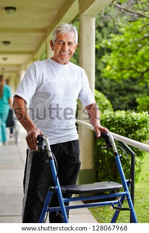 Happy senior man walking with a walker in the park of a clinic - stock photo