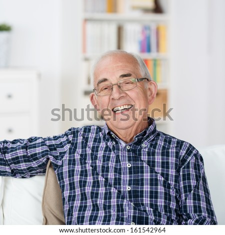 Happy senior man with a beaming smile wearing glasses sitting back relaxing in a chair at home - stock photo