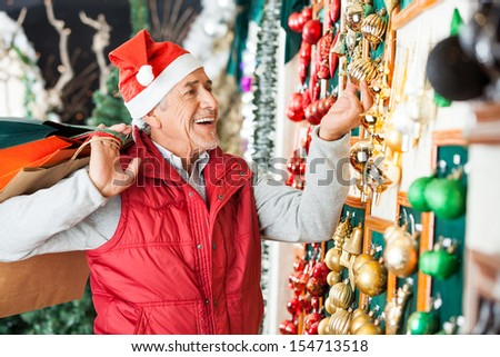Happy senior man with shopping bags buying Christmas ornaments at store - stock photo