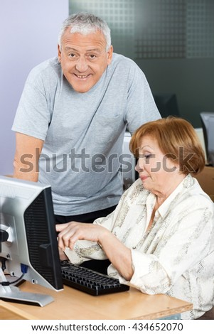 Happy Senior Man With Woman Using Computer In Classroom