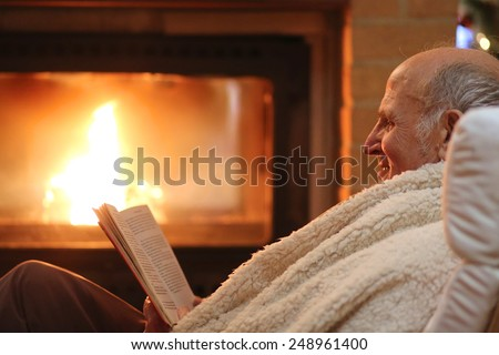 Happy senior man, wrapped in warm knitted plaid, relaxing at home in the evening, sitting in rocking chair by fireplace and reading a book - successful retirement concept - stock photo