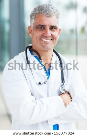 happy senior medical doctor with arms crossed in office - stock photo