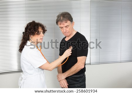 Happy senior patient and doctor at the doctor's office - stock photo