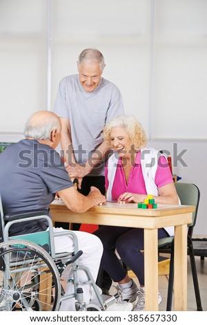 Happy senior people during rehab playing Bingo together - stock photo