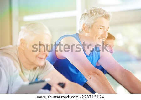 Happy senior people exercising on bikes in gym in summer - stock photo
