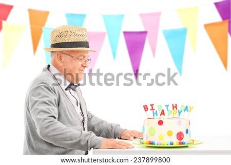 Happy senior sitting at a table with birthday cake isolated on white background - stock photo