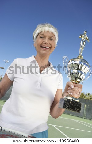 Happy senior tennis player holding trophy after winning - stock photo