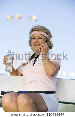 Happy senior tennis player with water bottle using cell phone