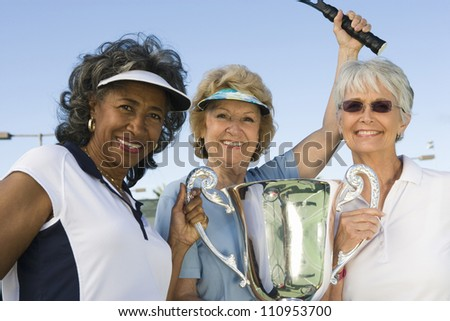 Happy senior tennis players holding trophy after winning - stock photo