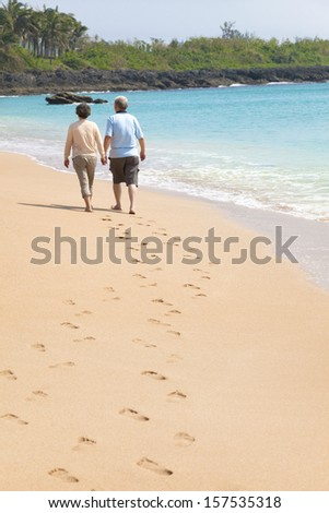 happy senior walking on the beach with footprint - stock photo