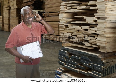 Happy senior warehouse worker talking on mobile phone