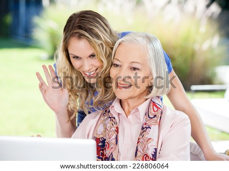 Happy senior woman and granddaughter video chatting on laptop at nursing home porch - stock photo