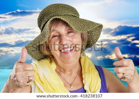 Happy senior woman at the beach two thumbs up