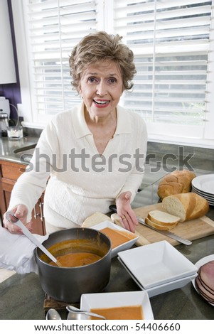 Happy senior woman cooking soup in kitchen