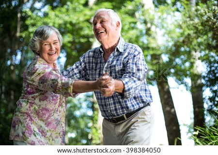 Happy senior woman dancing with husband against trees in back yard - stock photo