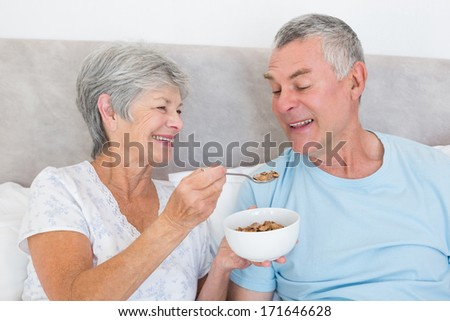 Happy senior woman feeding cereals to husband at home