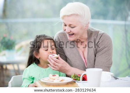 Happy senior woman feeding cookie to granddaughter at home - stock photo
