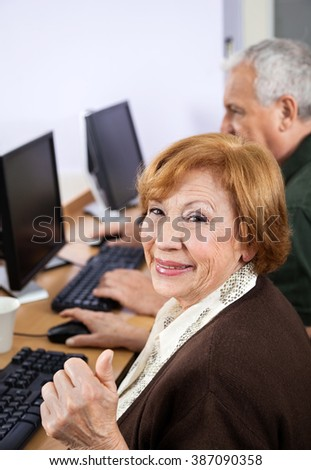 Happy Senior Woman Gesturing Thumbsup At Desk In Computer Class