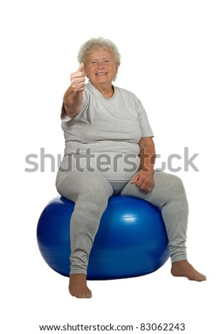 Happy senior woman gives OK on a fitball, on white background - stock photo