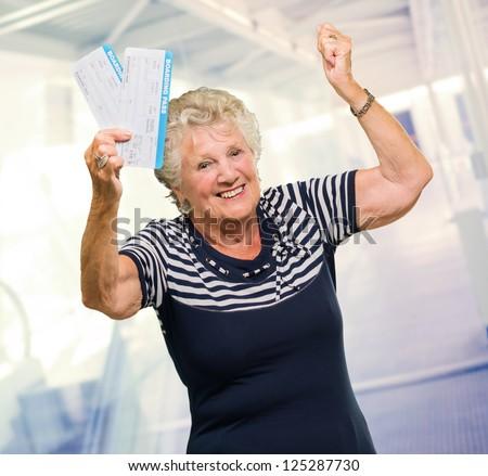 Happy Senior Woman Holding Boarding Pass, Indoors - stock photo
