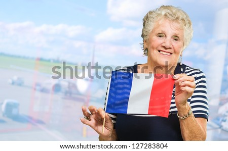 Happy Senior Woman Holding France Flag, Indoors - stock photo