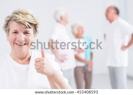 Happy senior woman holding her thumb up, group of fit seniors in the background