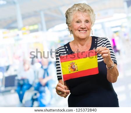 Happy Senior Woman Holding Spain Flag, Indoors - stock photo