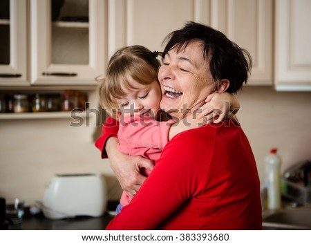 Happy senior woman hugging her beautiful grandchild - in kitchen at home - stock photo