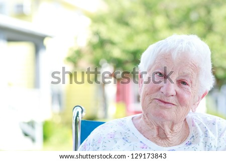 Happy Senior Woman in a Wheelchair Outside