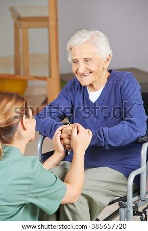 Happy senior woman in wheelchair holding hands with geriatric nurse