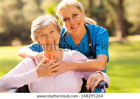 happy senior woman in wheelchair outdoors with caring caregiver - stock photo