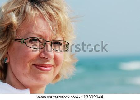 happy senior woman on summer vacation at sea - stock photo