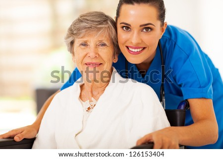 happy senior woman on wheelchair with caregiver - stock photo