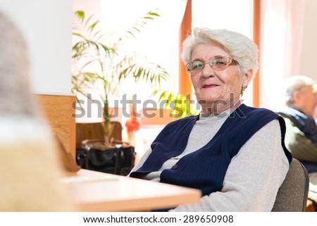 Happy senior woman playing rummy - stock photo