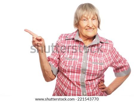 happy senior woman pointing upwards isolated on white background - stock photo
