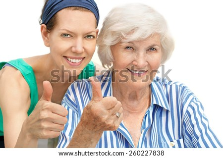 Happy senior woman portrait together with granddaughter, holding thumb up - stock photo
