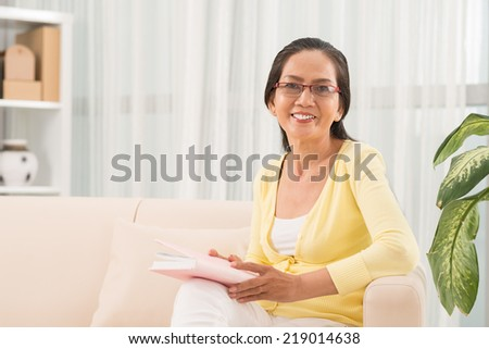 Happy senior woman reading a book at home - stock photo