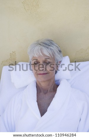 Happy senior woman relaxing in a spa with closed eyes - stock photo