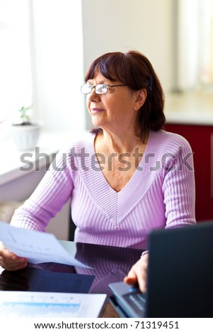 Happy senior woman sitting at the table and calculating her finances at home near the computer looking at the window - stock photo