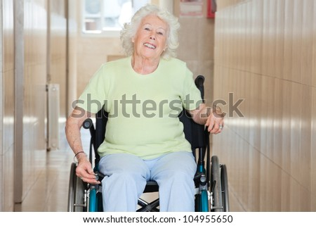 Happy senior woman sitting in a wheel chair at hospital corridor - stock photo
