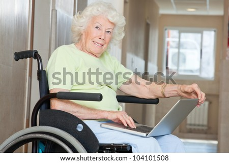 Happy senior woman sitting in wheelchair using laptop at hospital - stock photo