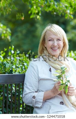 Happy  senior woman  sitting on a park bench - stock photo