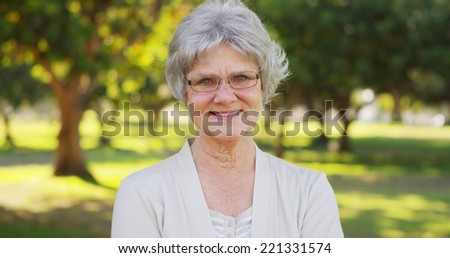 Happy senior woman standing in the park - stock photo