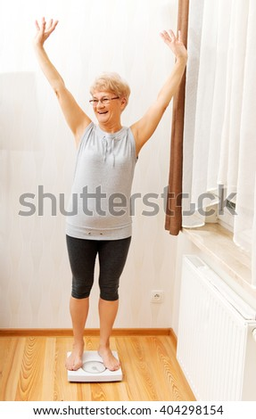 Happy senior woman standing on weight scale in living room - stock photo