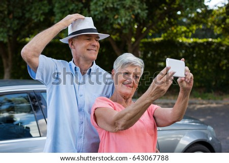 Happy senior woman taking selfie with man by car
