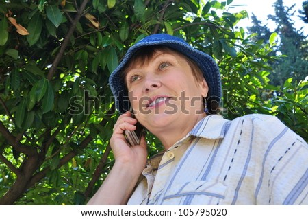 Happy senior woman talking on a cell phone in park