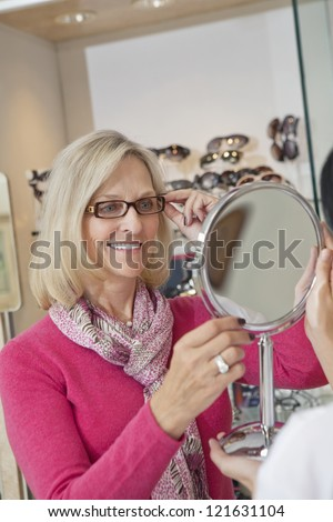 Happy senior woman trying on glasses while optician holding hand mirror